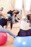 Fünf kaukasische weibliche Athleten, die das Ausdehnen von Übungen haben stockfotos