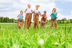 Fünf Kinder, die den Spaß springt in den Säcken haben Stockbilder