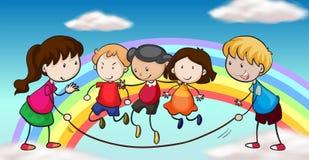 Fünf Kinder, die vor einem Regenbogen spielen Lizenzfreie Stockfotos