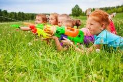 Fünf Kinderspiel mit Wasserwerfern lizenzfreies stockfoto