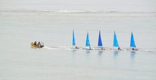 Fünf kleine bunte Segeln-Schlauchboote, die durch ein kleines aufblasbares Motorboot geschleppt werden Stockbild
