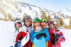 Fünf lächelnde Freunde mit Snowboards Stockbilder