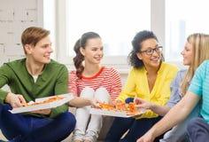 Fünf lächelnde Jugendliche, die zu Hause Pizza essen lizenzfreies stockfoto
