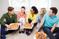 Fünf lächelnde Jugendliche, die zu Hause Pizza essen Stockfotografie