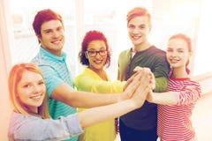 Fünf lächelnde Studenten, die in der Schule Hoch fünf geben stockfotografie
