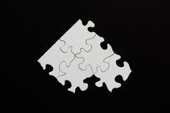 Fünf leere Puzzlespielstücke auf schwarzem Hintergrund Stockbild