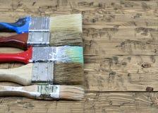 Fünf mehrfarbige Bürsten auf einem rustikalen Holztisch Stockfotografie