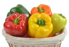 Fünf mehrfarbige Gemüsepaprikas im Weidenkorb, Nahaufnahme Stockbild