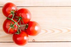 Fünf mittlere Tomaten über unfertigen hölzernen Planken Stockbilder