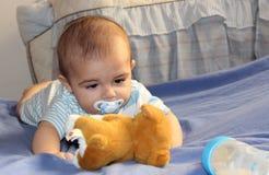 Fünf Monate alte Baby, die auf dem Bett spielen Stockbild