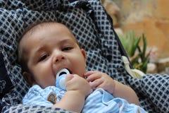 Fünf Monate alte Baby, die im Kinderwagen spielen Lizenzfreie Stockbilder