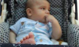 Fünf Monate alte Baby, die im Kinderwagen spielen Stockbild