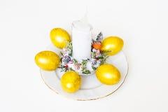 Fünf Ostereier und weiße Kerze auf dem Tisch Lizenzfreie Stockbilder