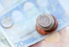Fünf Pennys prägen auf einem Stapel und Euroanmerkungen Stockfotografie