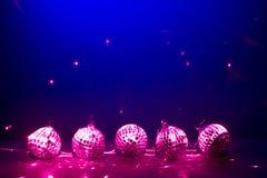 Fünf purpurrote Discokugeln reflectoin Leuchten Stockbild