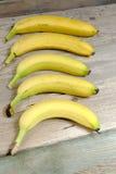 Fünf reife Bananen auf einem Holztisch Stockbilder