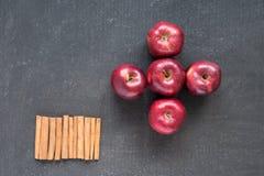 Fünf rote Äpfel und Zimt in der Reihe Stockfotografie