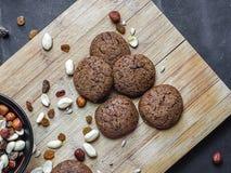 Fünf runde Schokoladenplätzchen auf dem hölzernen Schneidebrett mit schwarzem Tafelhintergrund lizenzfreies stockfoto