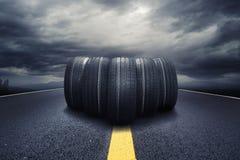 Fünf schwarze Reifen, die auf einer Straße mit Wolken rollen stockfotografie