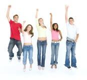 Fünf springende und lächelnde Freunde Stockbilder