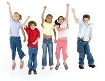 Fünf springende und lächelnde Freunde Stockfoto