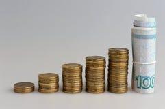 Fünf Stapel Münzen und Banknoten Stockbild