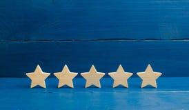Fünf Sterne auf einem blauen Hintergrund Das Konzept der Bewertung und der Bewertung Die Bewertung des Hotels, Restaurant, bewegl lizenzfreie stockbilder