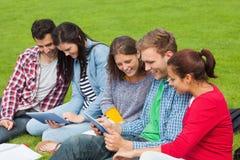 Fünf Studenten, die auf dem Gras unter Verwendung der Tablette sitzen Lizenzfreie Stockbilder