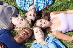 Fünf Studenten, die sich draußen entspannen Stockfoto