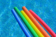 Fünf vibrierend, hell farbige Poolnudeln in einem Swimmingpool, keine Leute stockbild
