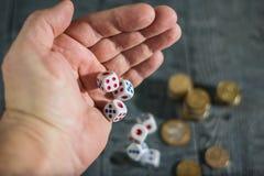 Fünf Würfel rollen mit linken Handmännern auf dem Tisch mit Geld stockfoto