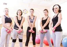 Fünf weibliche kaukasische Athleten, die mit Barbrells stehen stockbilder