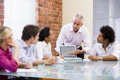 Fünf Wirtschaftler im Sitzungssaal mit Laptop Stockbilder