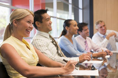 Fünf Wirtschaftler am Sitzungssaaltabellenlächeln Lizenzfreie Stockbilder