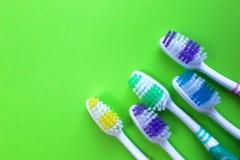 Fünf Zahnbürsten liegen auf einem grünen Hintergrund lizenzfreie stockbilder
