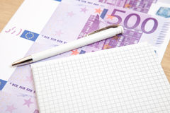 Fünfhundert Euroanmerkungen nahe bei Notizblock Lizenzfreie Stockfotos