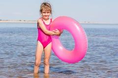 Fünfjahresmädchen im rosa Badeanzug, der mit Schwimmen steht, hüllt im Fluss ein Lizenzfreies Stockfoto