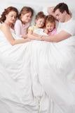 Fünfköpfige Familie, die unter Decke schläft stockbild