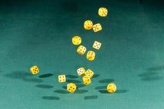 Fünfzehn gelb würfelt das Fallen auf eine grüne Tabelle stock abbildung