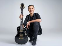 Fünfzehn Jahre alte Gitarrist mit einer schwarzen E-Gitarre lizenzfreies stockbild