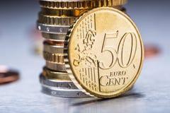 Fünfzig-Cent-Münze auf dem Rand Fokus auf Seil Fünf, 10 und fünfzig Eurobanknoten Euromünzen gestapelt auf einander in den versch Lizenzfreie Stockfotografie