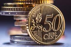 Fünfzig-Cent-Münze auf dem Rand Fokus auf Seil Fünf, 10 und fünfzig Eurobanknoten Euromünzen gestapelt auf einander in den versch Stockfotografie