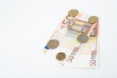 Fünfzig Euroanmerkungen lockerten Front mit verschiedenen Euromünzen auf Stockfotografie