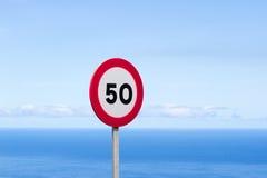 Fünfzig Verkehrszeichen 50 Meilen pro Stunde runde Rot des Höchstgeschwindigkeits-Zeichens gegen blauen Himmel Lizenzfreie Stockfotografie