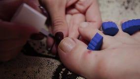 Für die Mädchenbeinpediküre sich interessieren, Politur, schöne Lichter Pediküren im Salon Die Hauptsorgfalt für die Nägel stock video