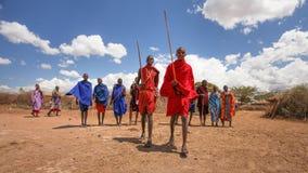 Für traditionelles Tanzen ausrichtende und singende Masaikrieger stockfotos