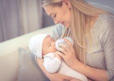 Fütterungsbaby der glücklichen Mutter Stockfoto