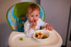 Fütterungsbaby - entzückender Junge, der Gemüse isst stockfotos