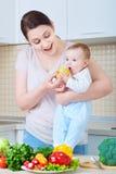 Fütterungsbabyapfel der jungen Mutter Eine glückliche Familie stockfotos