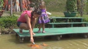 Fütterungsfische der Frau und der Tochter im Teich die Reserveweggänse Viele Fische stock video